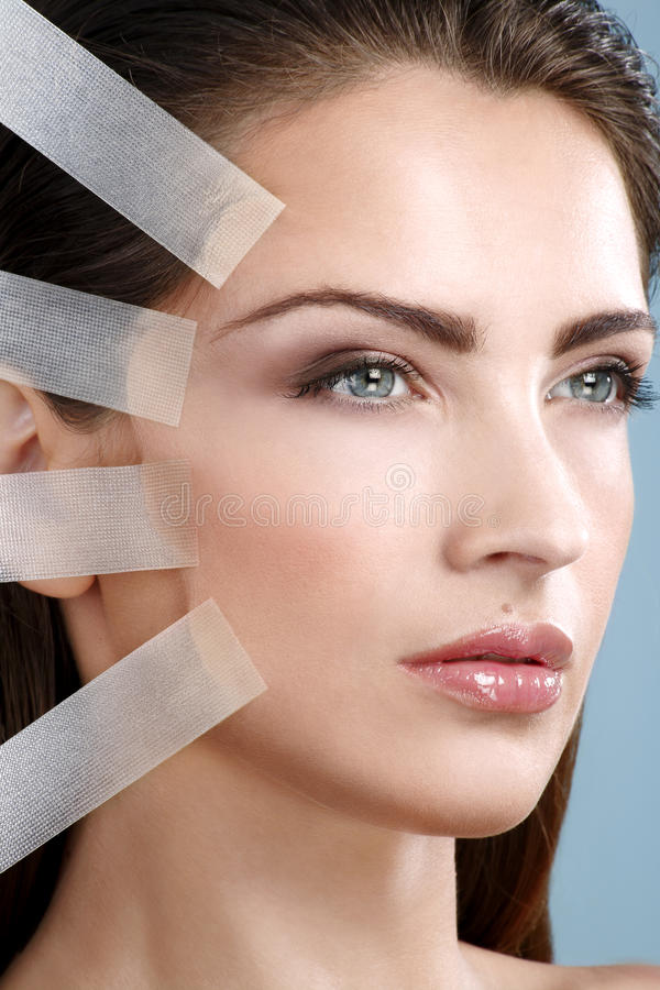 Beautiful woman applying tape lifting treatment on face. On blue background royalty free stock photos