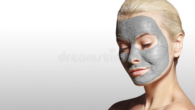 Beautiful Woman Applying White Facial Mask. Beauty Treatments. Spa Girl Apply Clay Facial mask on grey background stock image