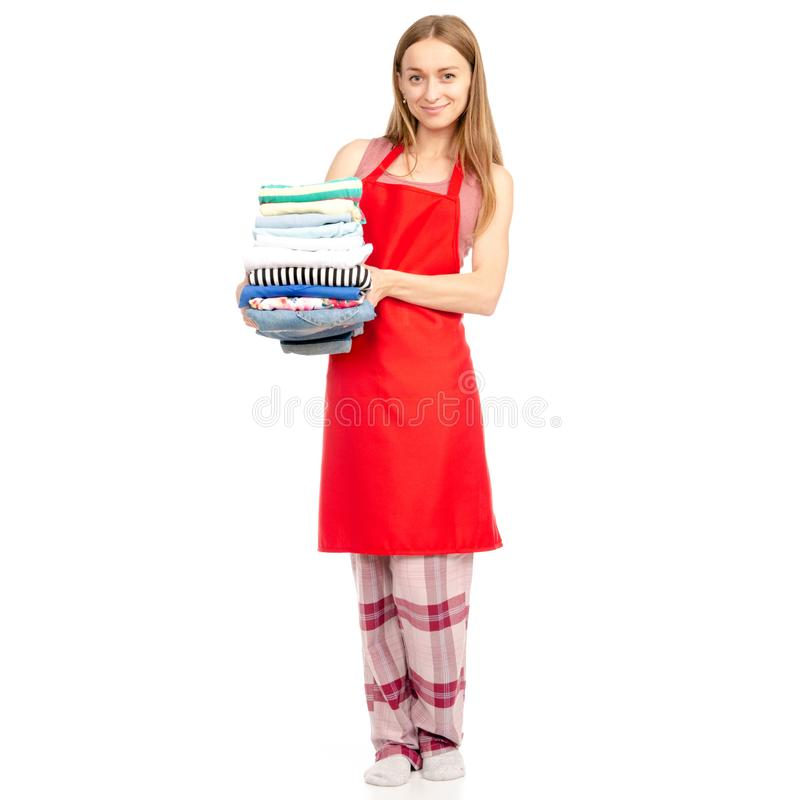 Beautiful woman in apron stack towels ironed clean clothes in hand. On white background isolation stock photography