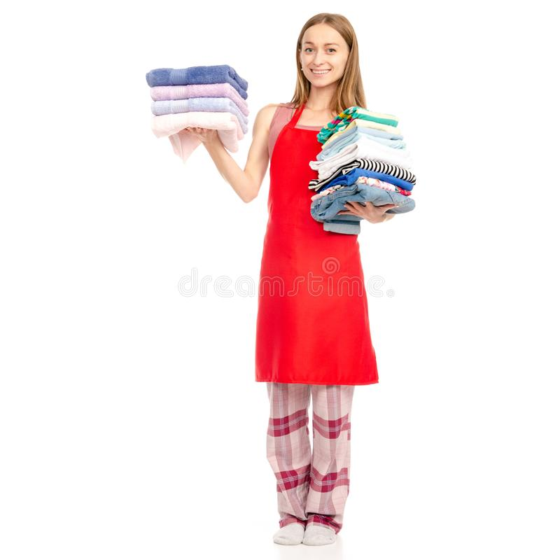Beautiful woman in apron stack towels ironed clean clothes in hand. On white background isolation royalty free stock image