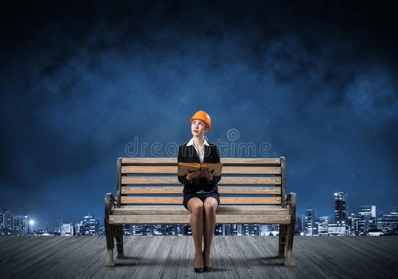 Beautiful woman architect sitting on wooden bench stock image