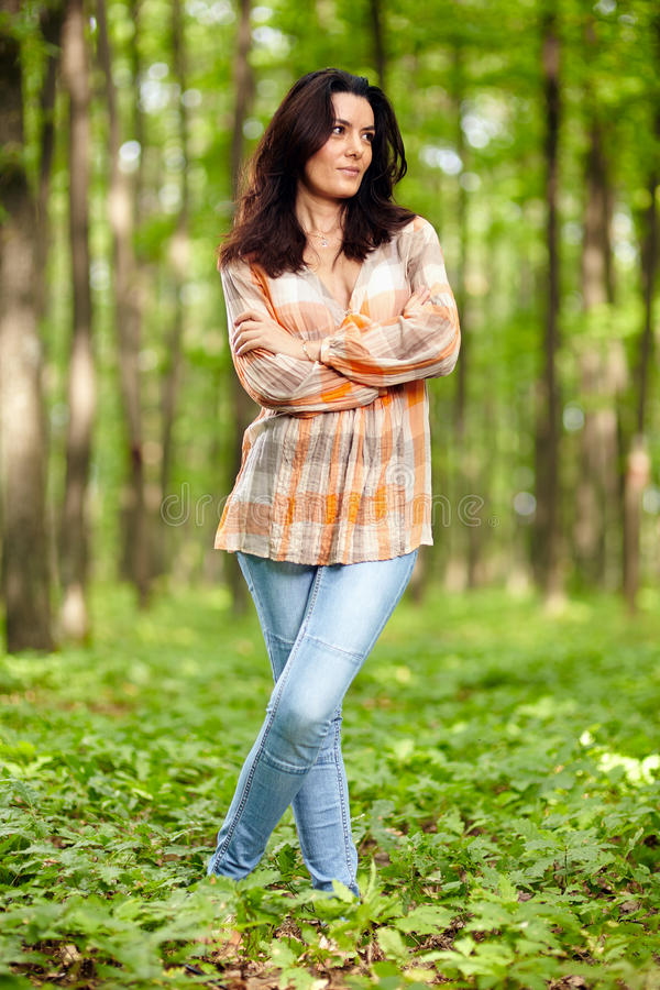 Beautiful woman with arms folded in a forest. Beautiful woman with arms folded standing in a forest stock photos