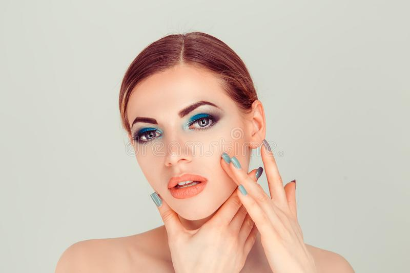 Woman with artistic green makeup hairdo, perfect skin and nails royalty free stock image