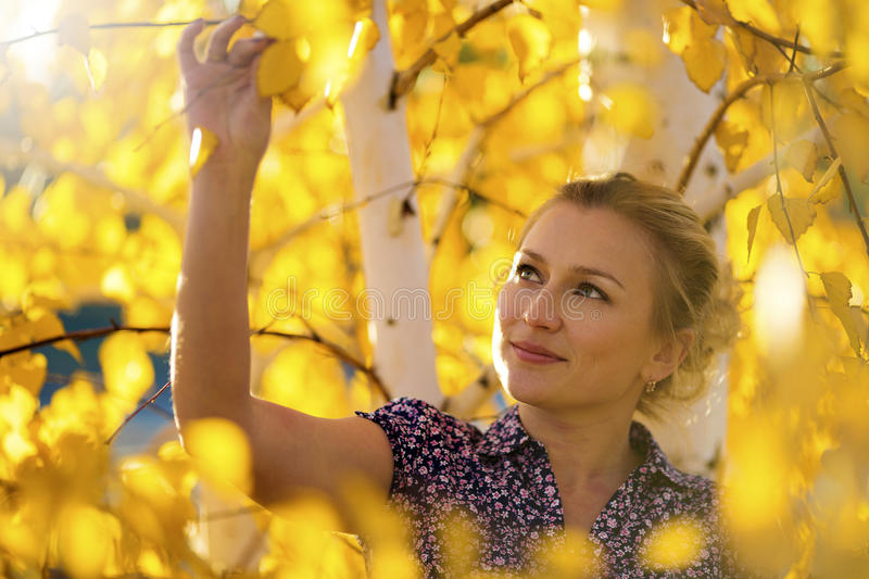 Beautiful woman in autumn park. With yellow leaves royalty free stock image