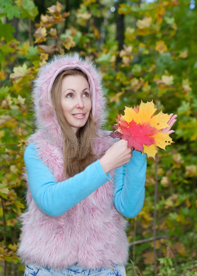 beautiful woman in autumn park with an armful of maple leaves royalty free stock image