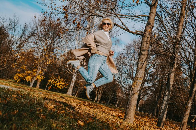 Beautiful woman in autumn park jumping and smiling. Sunny day stock photography