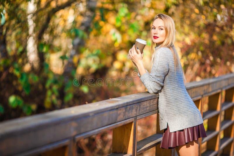 Fall concept - beautiful woman drinking coffee in autumn park under fall foliage. Beautiful woman in autumn park under fall foliage at warm day royalty free stock image