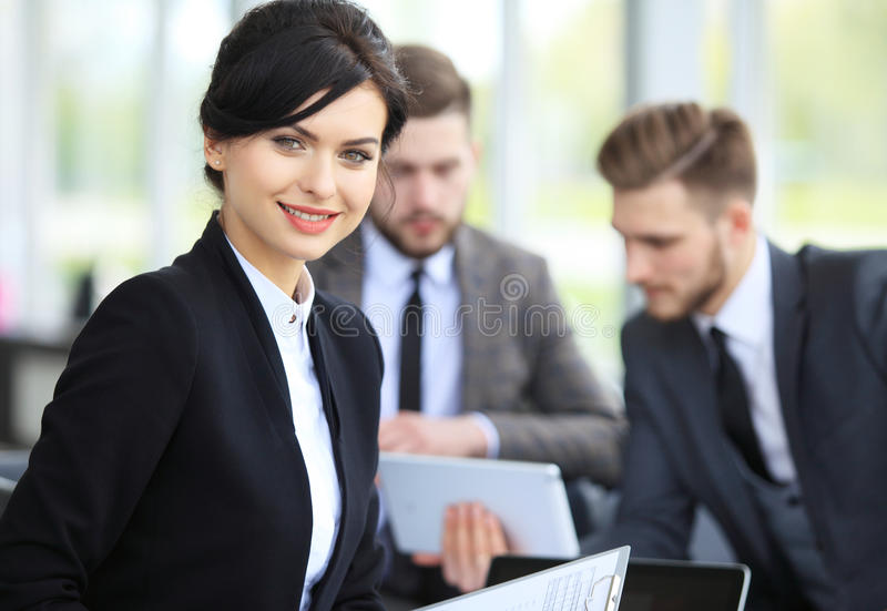 Beautiful woman on the background of business people. Face of beautiful women on the background of business people royalty free stock photography