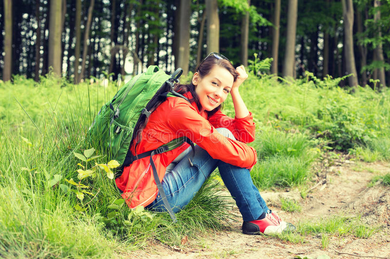 Beautiful woman with backpack in a forest having a break royalty free stock photos