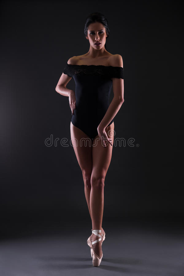 Beautiful woman ballerina in black body suit posing on toes over. Black background stock photo