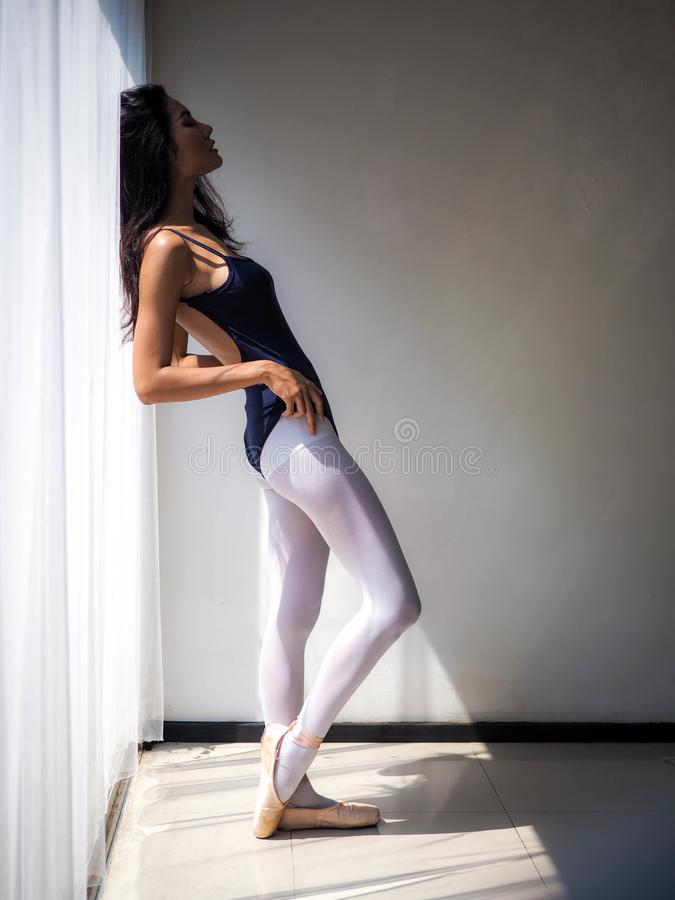 Beautiful woman ballet dancer standing post against the window, Beautiful pose.  stock images