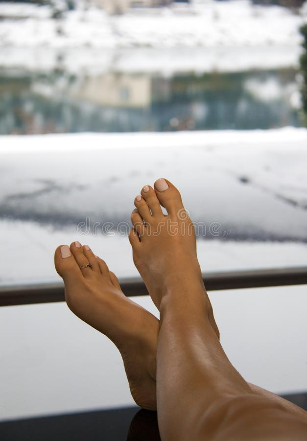 Beautiful woman bare feet up on the table in warm classy interior with large glass window and luxury view of the snowy landscape royalty free stock images