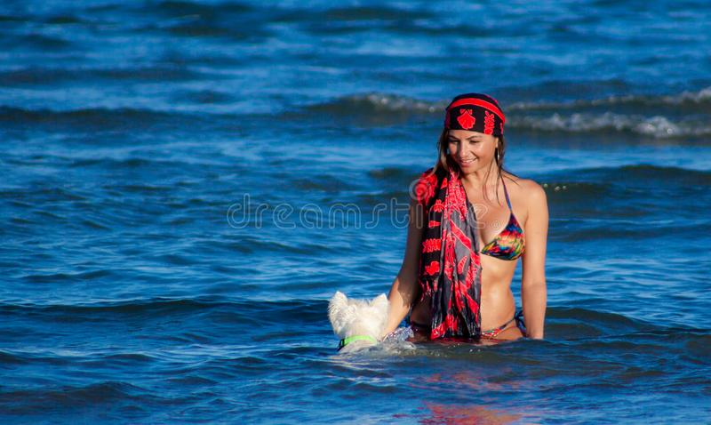Beautiful woman in a bathing suit and brunette together while she is in the water on the beach in Sottomarina Chioggia together wi royalty free stock image