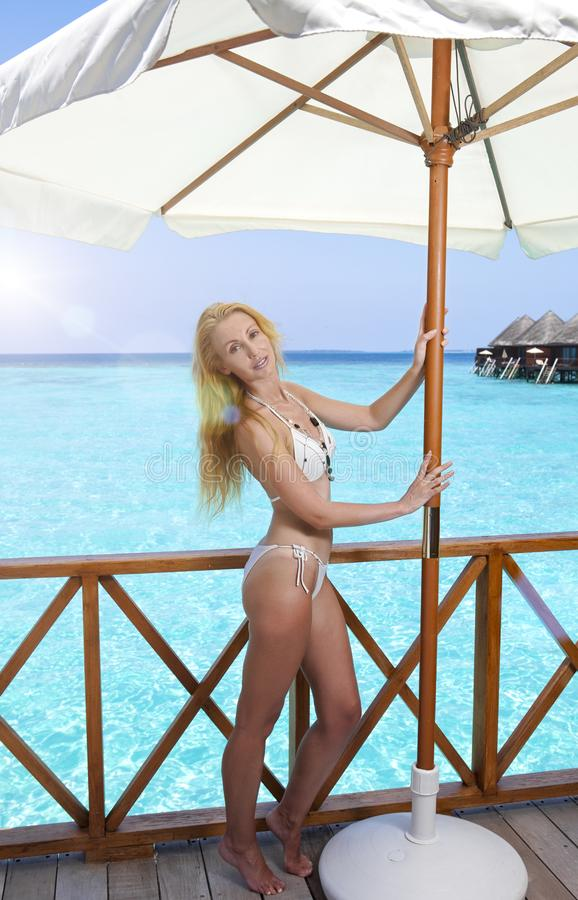 Beautiful woman in bathing suit under a sun protection umbrella on a wooden terrace and the sea on a background, Maldives royalty free stock photos