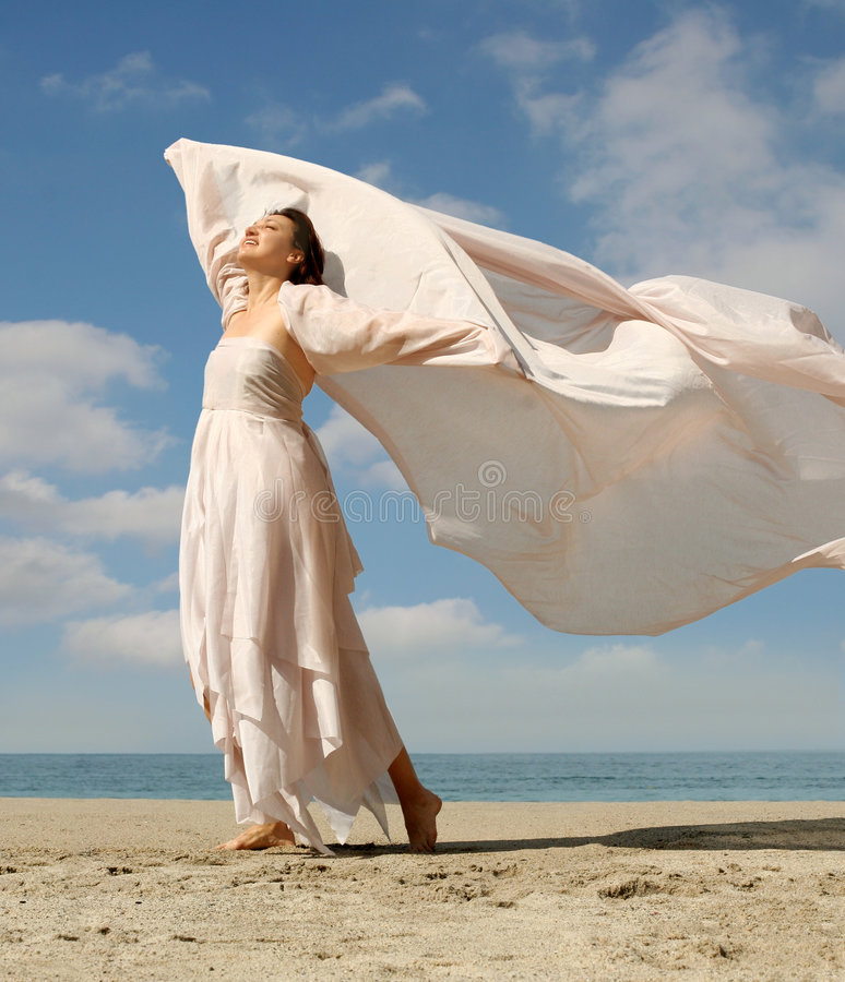 Beautiful woman on the beach. Happy woman with a scarf standing on the beach stock images