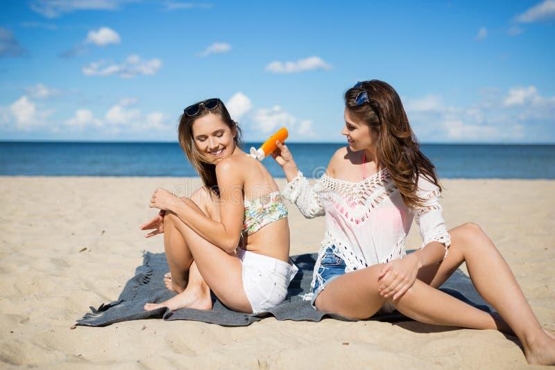 Beautiful woman on beach applying suntan oil on friend royalty free stock photography