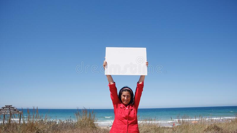 Beautiful woman in the beach with a blank sheet stock photos