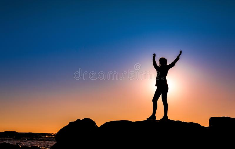 Woman on top a of the rock. Beautiful woman at the beach on top a of a rock in silhouette stock photography