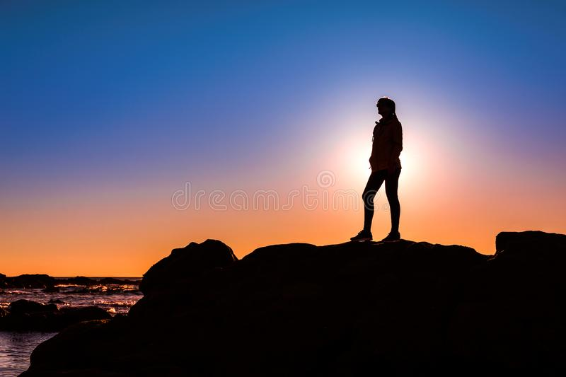 Woman on top a of the rock. Beautiful woman at the beach on top a of a rock in silhouette royalty free stock photos