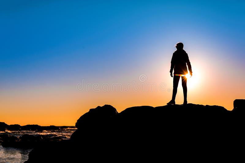 Woman on top a of the rock. Beautiful woman at the beach on top a of a rock in silhouette stock photos