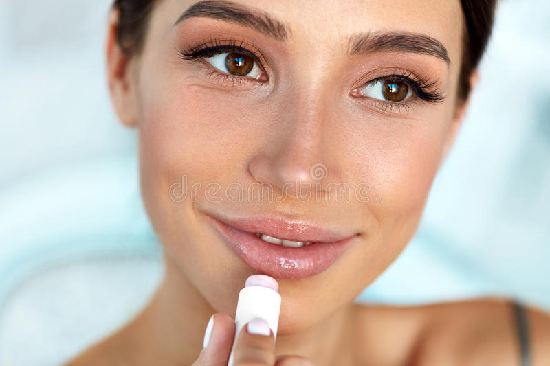 Beautiful Woman With Beauty Face Applies Balm On Lips. Skin Care stock image