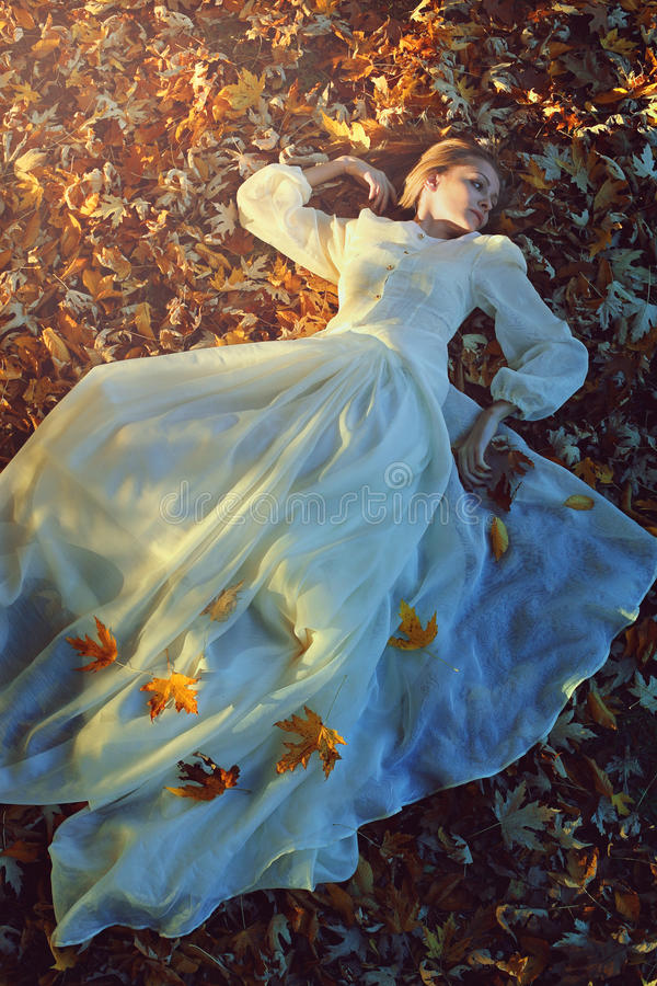 Beautiful woman on a bed of leaves stock photo