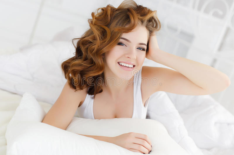Beautiful woman in bed in the morning. Young beautiful redhead woman with long curly hair ,dressed in a white nightgown wakes up in the morning on a soft pillow royalty free stock photography