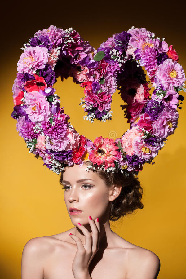 Beautiful woman with big floral heart on her head. Beautiful attractive caucasian woman with big floral heart on her head royalty free stock photography