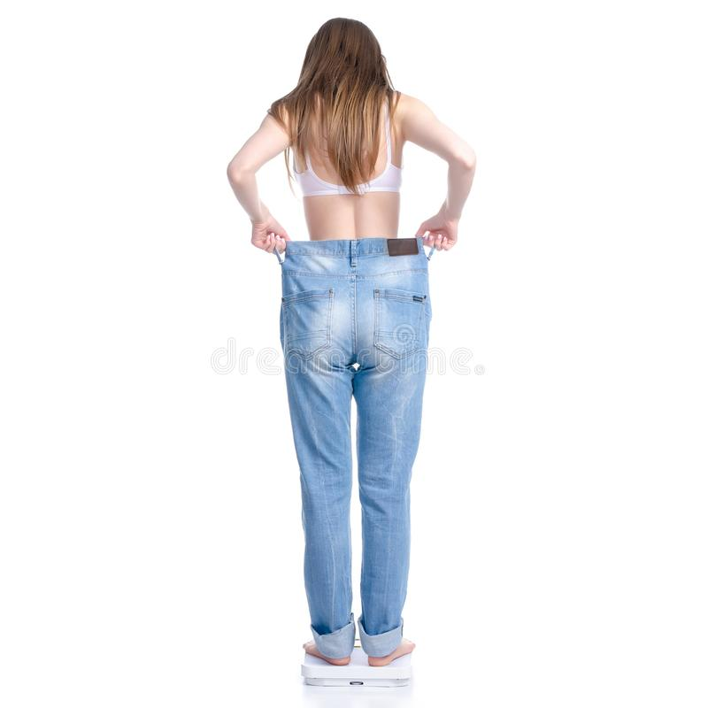 Beautiful woman in big jeans on weighing-machine, weight loss slimming royalty free stock photo