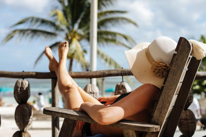 Beautiful woman with big summer hat and cigar. Woman in white hat and with cigar standing in water on caribbean beach stock photos
