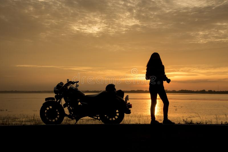 Beautiful Woman biker enjoying sunset, female riding motorcycle. motorbike driver traveling the world, Relaxing after long trip, f royalty free stock photo