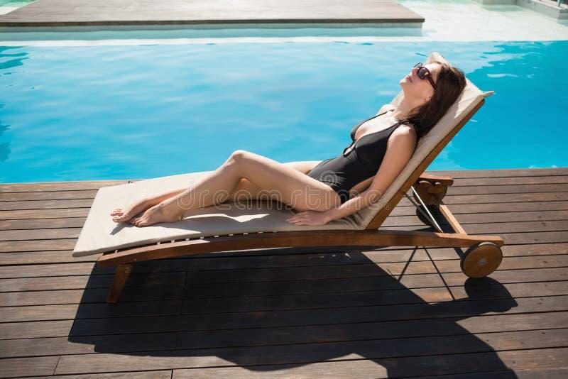 Beautiful woman in bikini relaxing by swimming pool stock photo