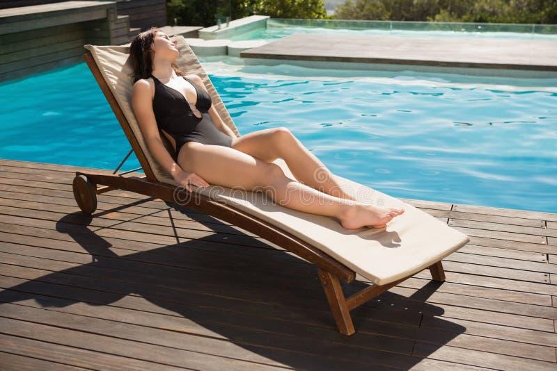 Beautiful woman in bikini relaxing by swimming pool royalty free stock images