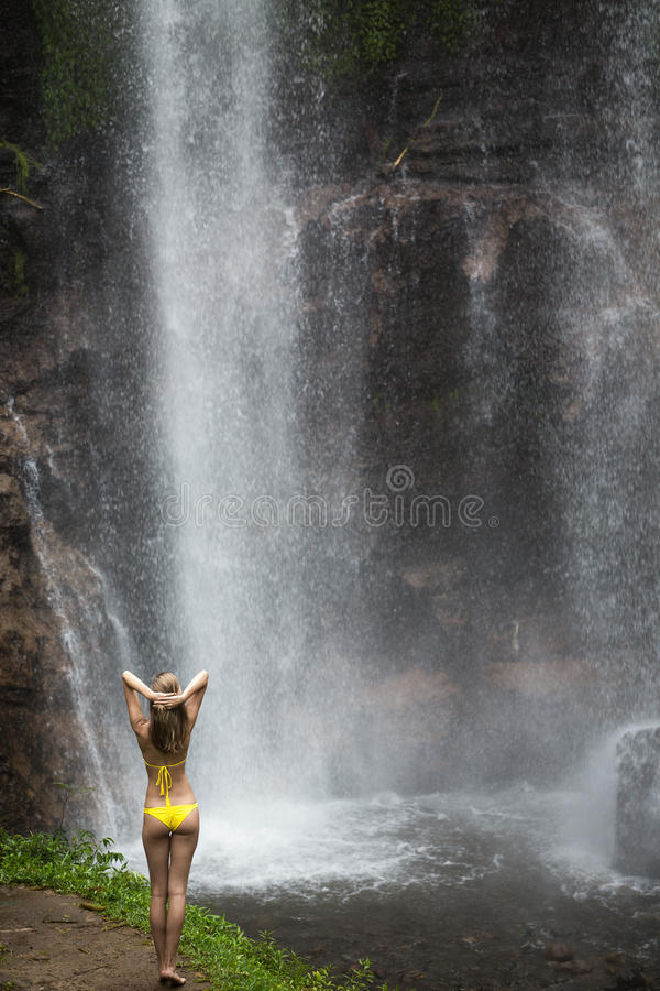 Beautiful woman in bikini and waterfall. stock photo