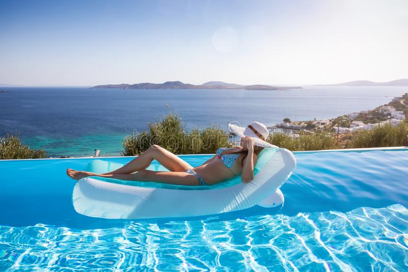 Woman enjoys the view to the Aegean Sea floating on a swimming pool, Mykonos, Greece stock photos