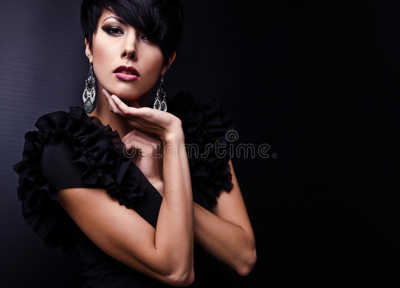 Beautiful woman on black classical dress pose in studio. Photo stock photography
