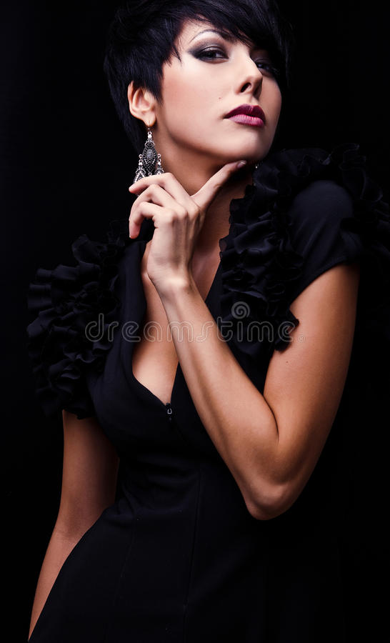 Beautiful woman on black classical dress pose in studio. Photo royalty free stock images