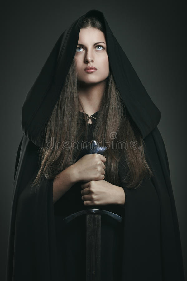 Beautiful woman with black cloak and sword royalty free stock photography