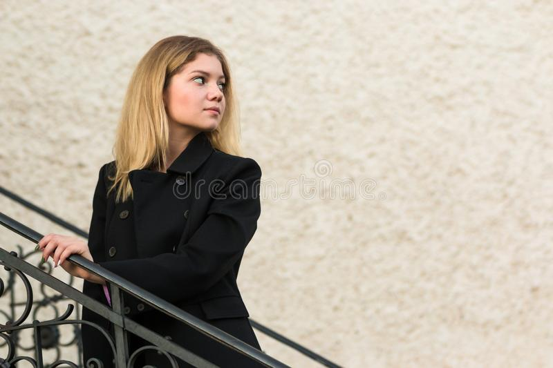 Beautiful Woman in black coat on old stairs of castle on wall Background stock images