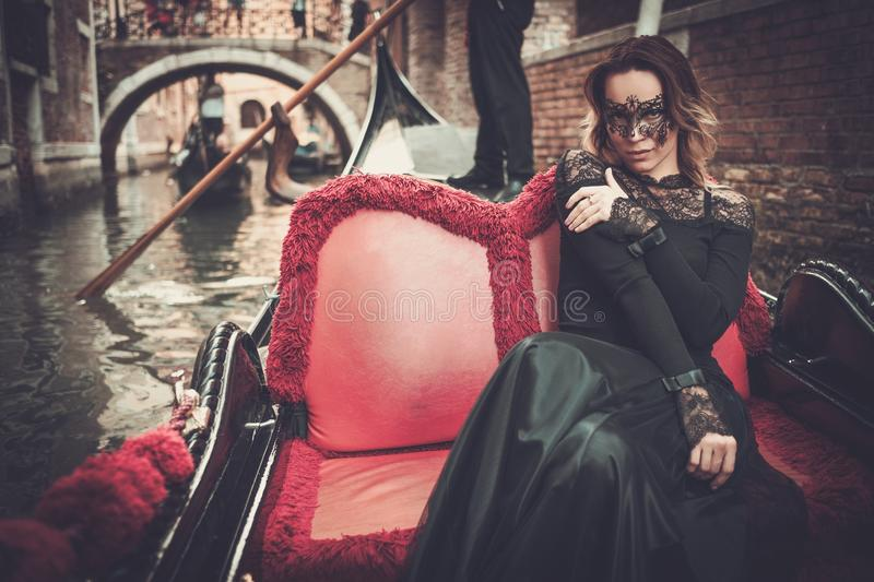 Beautiful woman in black dress with carnaval mask riding on gondola. stock image