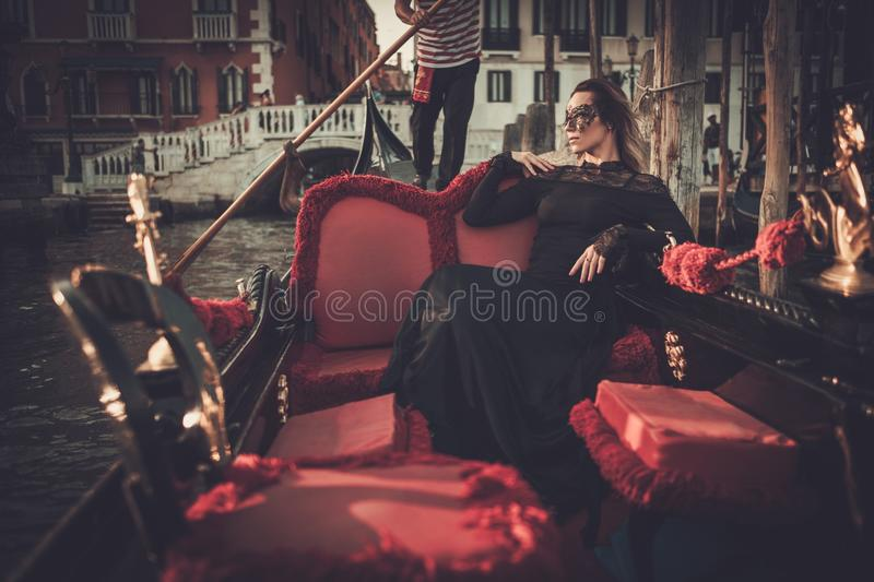 Beautiful woman in black dress with carnaval mask riding on gondola. Beautiful woman in black dress with carnaval mask riding on gondola, Venecia royalty free stock image