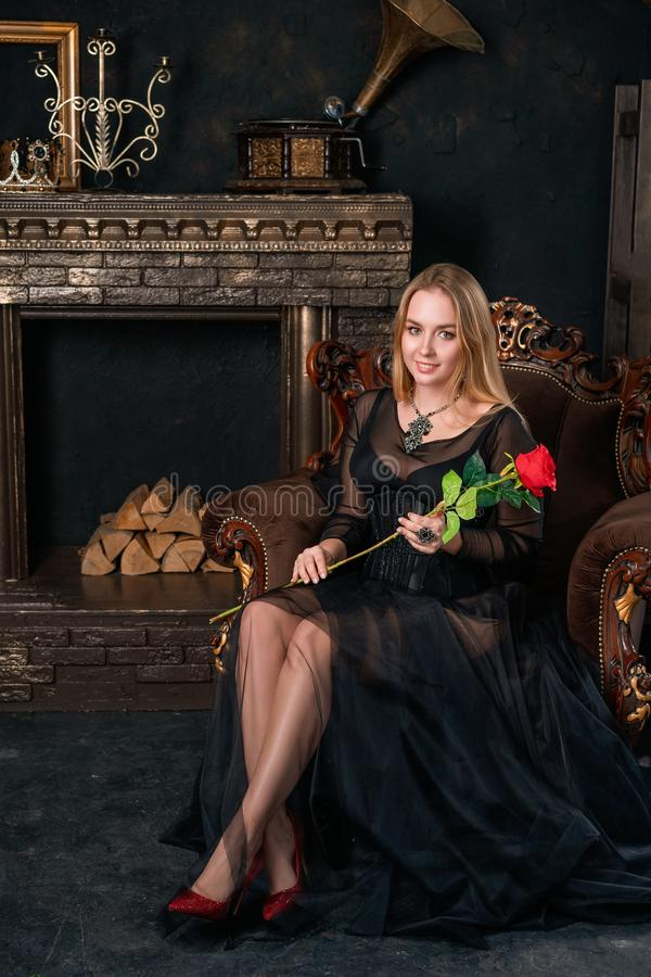 A beautiful woman in a black dress with a corset sitting on a chair in red shoes stock image