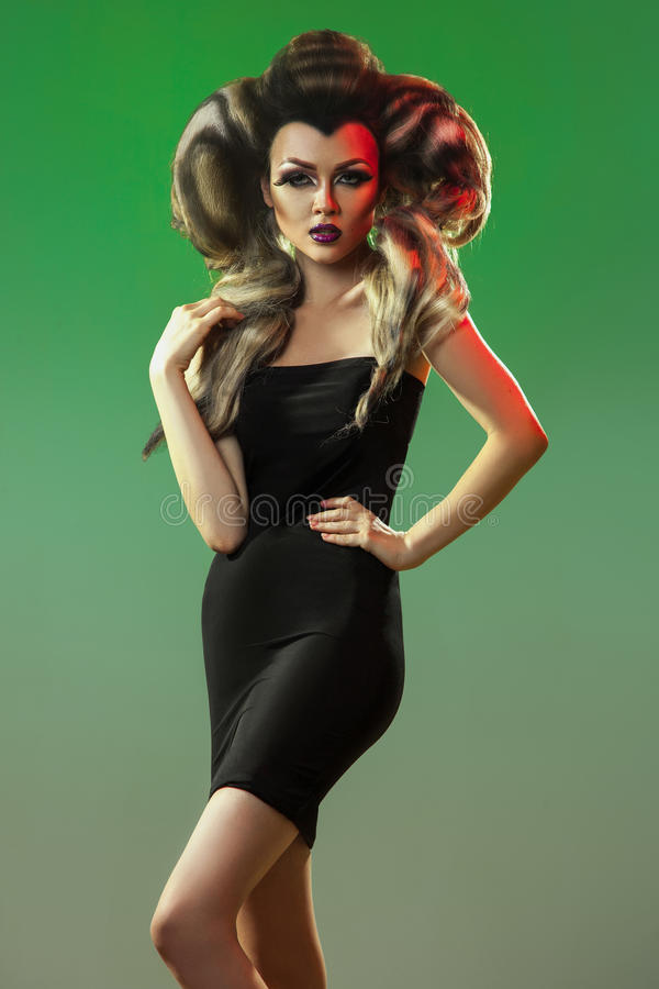 Beautiful woman in black dress and creative hairstyle looking at. Camera on green background in studio royalty free stock photos