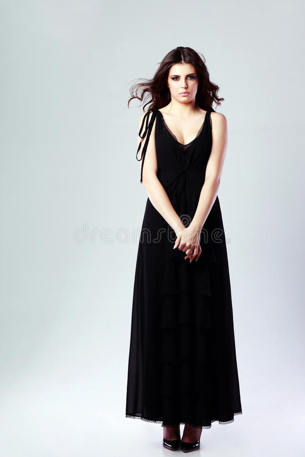 Beautiful woman in black dress. Full length portrait of a beautiful woman in black dress on gray background royalty free stock photography