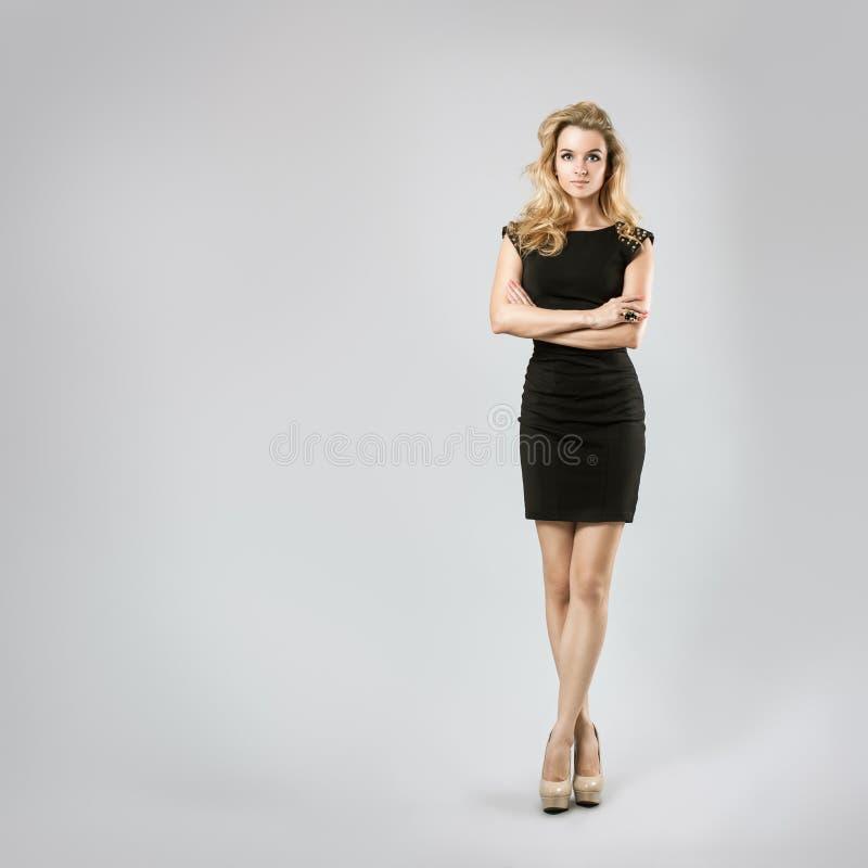 Beautiful Woman in Black Dress on Gray Backgound stock image