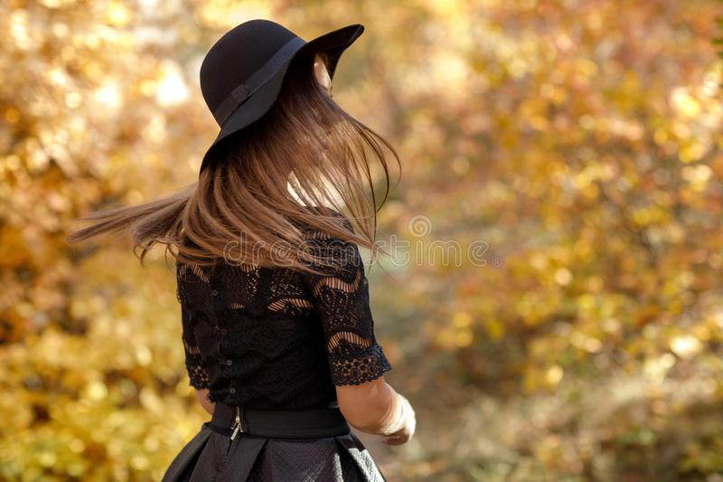 Beautiful woman in black dress and hat in autumn stock photography