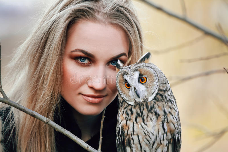 Beautiful woman in a black dress with an owl on his arm. Blonde with long hair in nature holding a owl. Romantic delicate girl. Beautiful woman in a black dress royalty free stock image