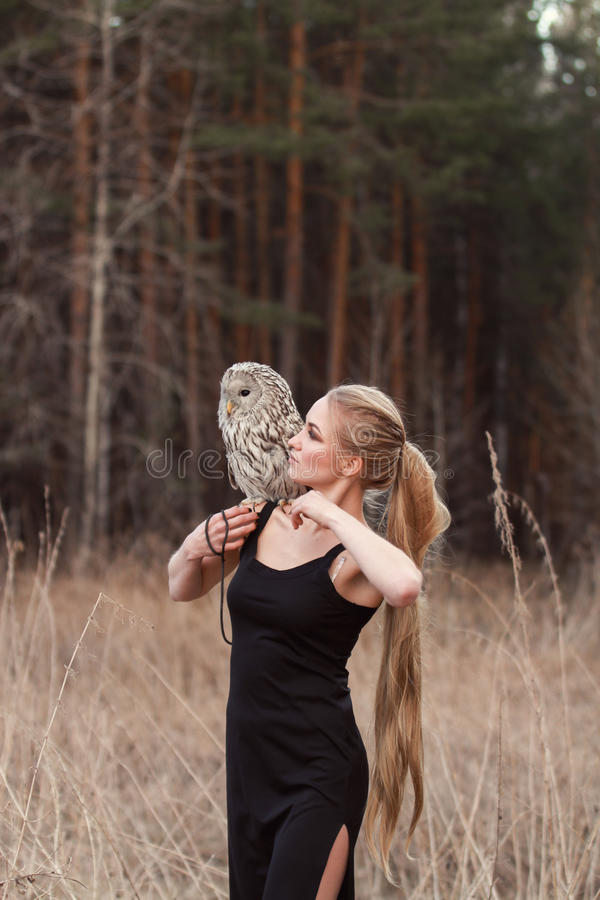 Beautiful woman in a black dress with an owl on his arm. Blonde with long hair in nature holding a owl. Romantic delicate girl. Beautiful woman in a black dress royalty free stock images