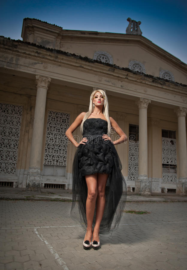 Beautiful woman in black dress posing outdoor. woman in stylish retro scene. Elegant woman in front of a castle. Portrait royalty free stock photography