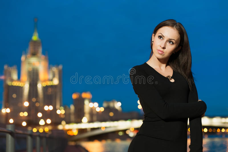 Beautiful woman in black dress standing on the waterfront stock photo